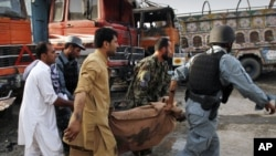 People carry a victim of a bomb attack in Jalalabad on May 18.