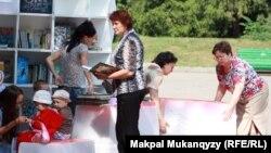 Алматыда ұйымдастырылған мобильді кітапхана оқырмандары. 12 шілде 2012 жыл. (Көрнекі сурет)