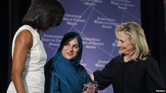 First Lady Michelle Obama (left) and U.S. Secretary of State Hillary Clinton (right) congratulate Shad Begum of Pakistan during the U.S. State Department's 2012 International Women of Courage Award winners' ceremony on March 8.