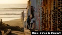 Человек перелезает через стену на американо-мексиканской границе, 24 декабря 2018 г.