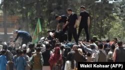 Люди, бежавшие в Кабул от наступающих талибов, на раздаче еды в афганской столице