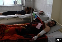 Afghan men are treated in a hospital after being injured in a car-bomb attack in Kabul on July 24.