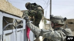Iraqi and U.S. soldiers search a house in Diyala governorate