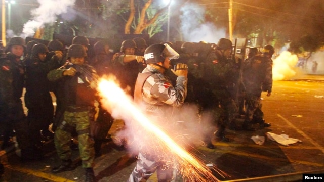 A riot policeman fires his weapon while confronting stone-throwing demonstrators during an antigovernment protest in Belem, Brazil, at the mouth of the Amazon River, on June 20.