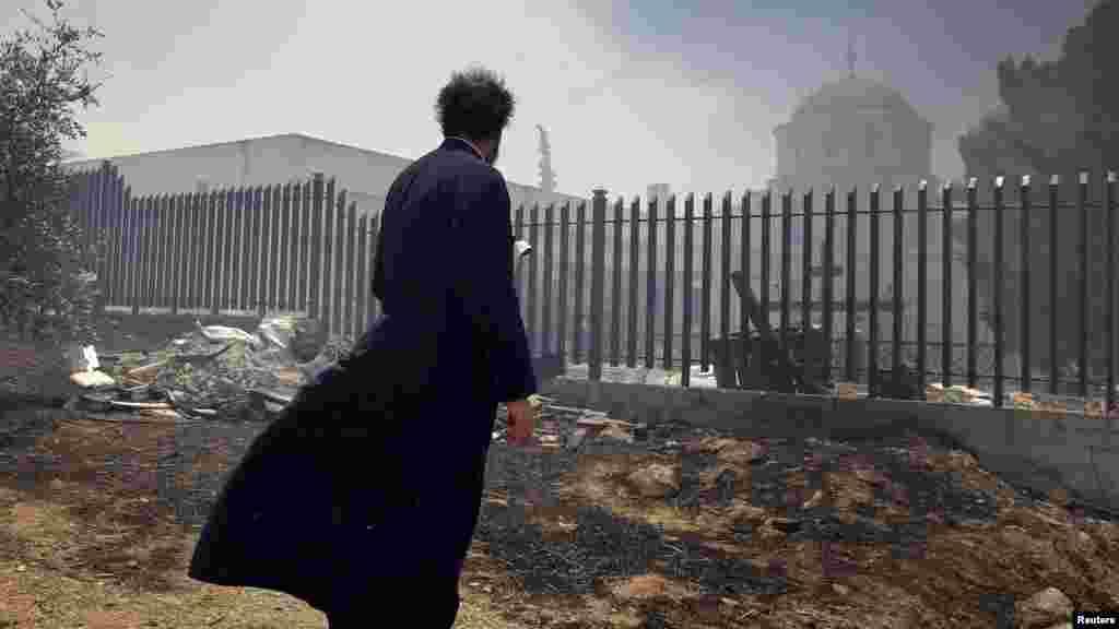 یک کشیش یونانی، در یکی از محلات آتن، که به خاطر حریق جنگلی ناچار شده از کلیسای خود فاصله بگیرد.