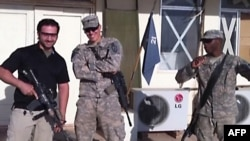 A TV grab shows a man (left) believed to be Amir Mirza Hekmati posing with U.S. troops at an unspecified location.