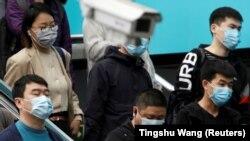 Пекиндегі метро станциясында бақылау камерасының қасынан өтіп бара жатқан жолаушылар. Қытай. 7 сәуір, 2020 жыл.