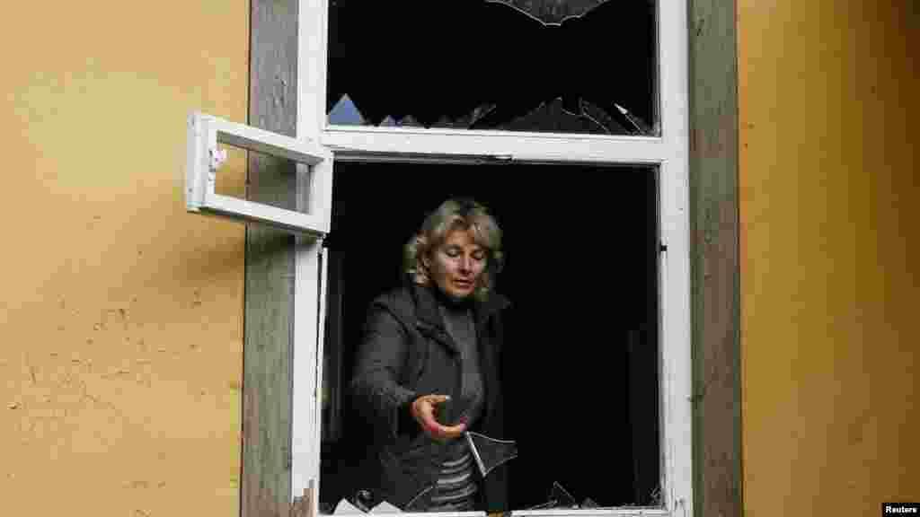 52-летняя Валентина Петренко смотрит из разбитого взрывной волной окна своего дома в поселке Дружба, расположенном неподалеку от складов боеприпасов.