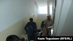 Конвойные поднимают заключенную Гаухар Худабаеву по лестнице в районной больнице. Поселок Отеген-батыра, Алматинская область, 20 июня 2019 года.