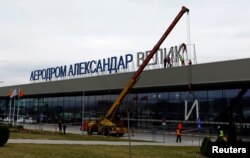 "Workers dismantle an ""Alexander the Great"" sign from the airport in Skopje on February 24 as a gesture of goodwill toward Greece."