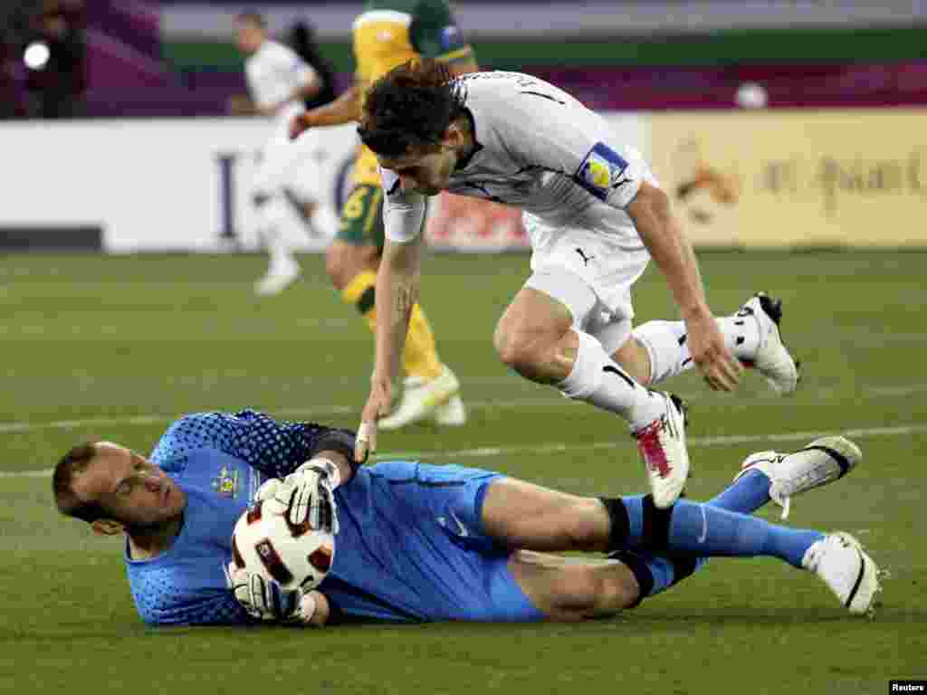 Qatar -- Australia vs. Uzbekistan at the 2011 Asian Cup semi-final soccer match in Doha, 25Jan2011 - Australia's goalkeeper Mark Schwarzer (L) makes a save against Uzbekistan's Server Djeparov during their 2011 Asian Cup semi-final soccer match at Khalifa stadium in Doha January 25, 2011. REUTERS/Suhaib Salem (QATAR - Tags: SPORT SOCCER)