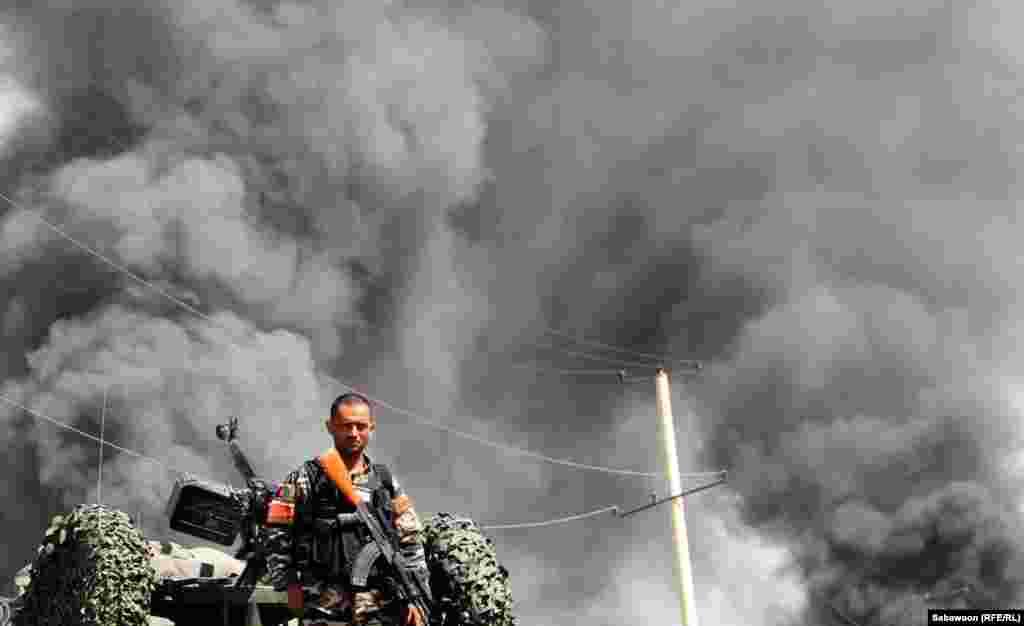 Афганский военнослужащий на месте теракта в пригороде Кабула 2 мая. Теракт произошел через несколько часов после того, как президент США Барак Обама покинул афганскую столицу, подписав соглашение о 10-летнем стратегическом партнерстве между США и Афганистаном. Движение талибов осудило договор. (RFE/Сабавун)