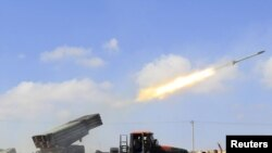 Rebel fighters fire a rocket west of the rebel-held city of Misurata on June 17.
