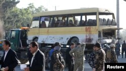 Afghan security forces inspect the damage of a minibus that was hit by a suicide attacker in Kabul on June 20.