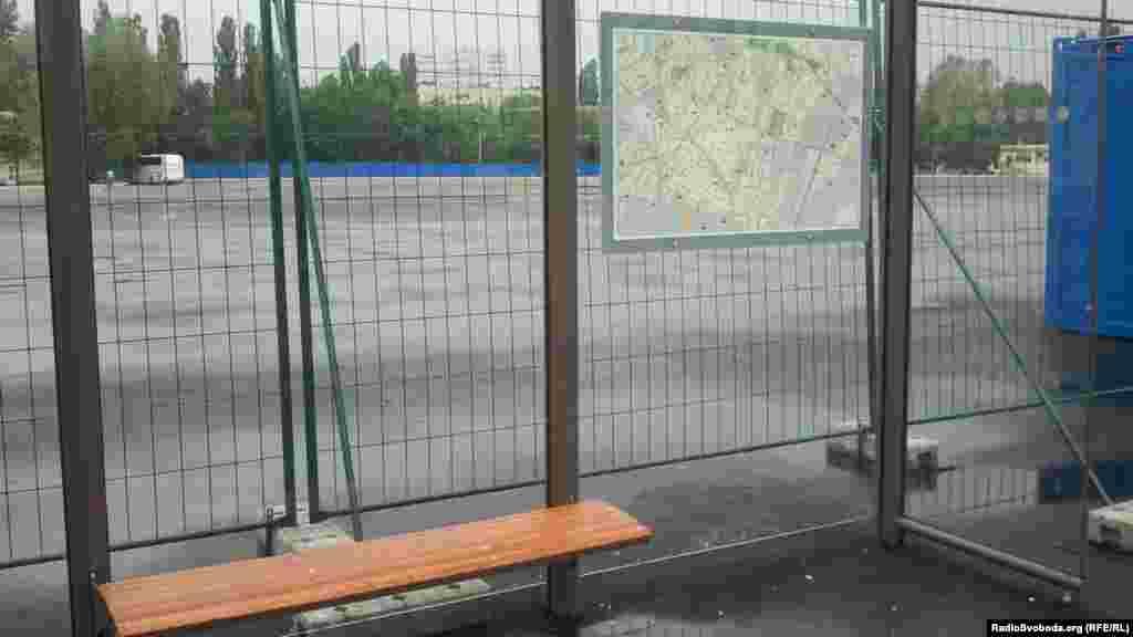 На трамвайній зупинці навпроти стадіону карта місцевості з надписами російською мовою