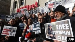 """Turkish journalists hold placards with images of Bunyamin Aygun, a photographer working for Istanbul daily """"Milliyet,"""" who was abducted in Syria by armed opposition groups, during a protest in Ankara on December 23, 2013."""