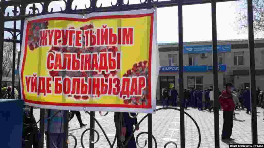 Баннер на воротах отделения Казпочты гласит: «Гулять запрещено». С самого утра у входа в это отделение собираются люди и встают в очередь. 6 апреля 2020 года.