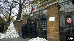 U.K. -- Police stand guard as structures made from white mannequin 'limbs' are pictured outside the Russian Embassy in west London, November 3, 2016