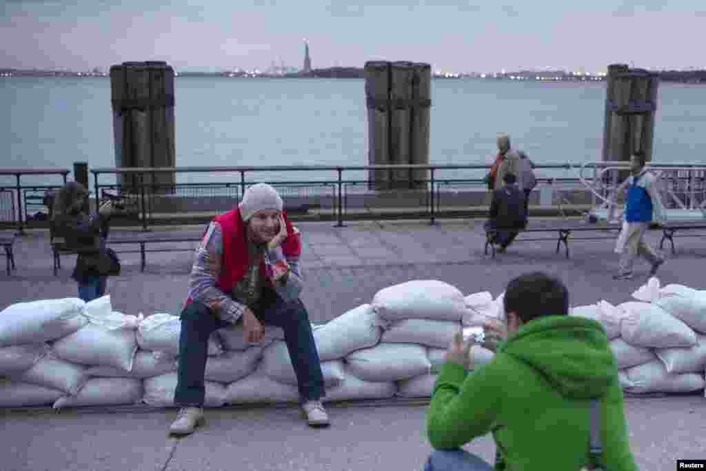 The Statue of Liberty is seen in the background as tourists from Russia pose for pictures on top of sand bags protecting Battery Park in Lower Manhattan, New York.