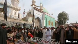 Relatives gather to attend funeral prayers on February 17 for victims killed in a suicide blast at the tomb of Sufi saint Syed Usman Marwandi, also known as the Lal Shahbaz Qalandar shrine, in Sehwan Sharif, Pakistan's southern Sindh Province.