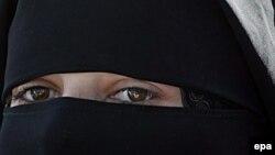 Женщина в парандже черного цвета.