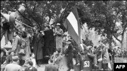 Мешканці Будапешта з угорським прапором на захопленому радянському танку під час придушення угорського повстання. 12 листопада 1956 року