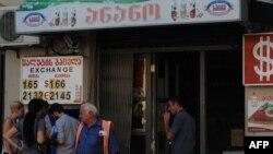 Люди рядом с пунктом обмена валют в Тбилиси.