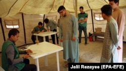 FILE: Afghan men get registered as voters at a voter registration center in Herat.