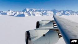 A NASA photo shows the wing of a DC-8 as it flies past Antarctica's tallest peak, Mount Vinson, during research on polar warming in 2012.