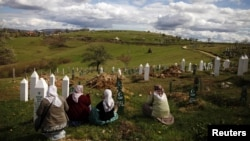 Muslim women in the town of Vlasenica, in an ethnically Serbian part of Bosnia-Herzegovina, sit before a mass funeral in April 2012 for victims of the Bosnian conflict.