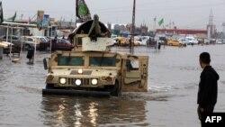 عربة عسكرية وسط شارع في بغداد غمرته الأمطار