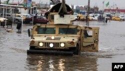 عربة عسكرية في شارع غارق بمياه الأمطار في بغداد