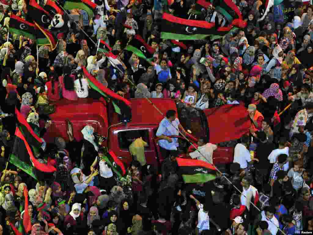 In the eastern city of Benghazi, people wave flags of the Kingdom of Libya, which predated Qaddafi, as they gather near the city's courthouse.