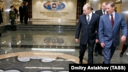 President Vladimir Putin and then Defense Minister Sergei Ivanov cast sidelong glances at the traditional GRU logo. (file photo)