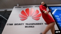 File photo: Belgium - A woman walks past a logo at the entrance of the European Huawei Cyber Security Transparency Centre during its opening in Brussels on March 5, 2019.