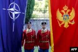 Montenegrin honor guards stand next to NATO and Montenegrin flags during a ceremony in the capital, Podgorica, in 2017, the year Montenegro joined the alliance.
