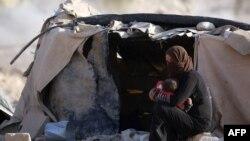 Сирияның солтүстік-шығысындағы Хасаке провинциясында босқындар лагерінде отырған сириялық босқын әйел.
