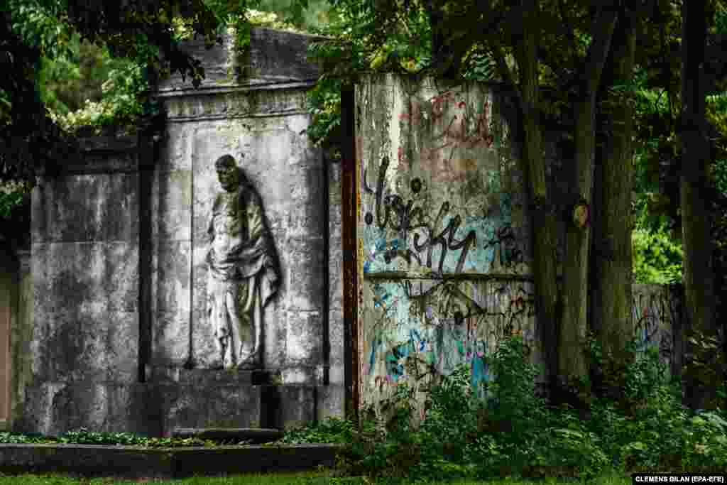 Remains of the former backcountry part of the Berlin Wall (R) stands next to a grave showing a Jesus figure on the site of the St. Hedwig cemetery stand in between trees and bushes in Berlin, Germany, 28 July 2021.
