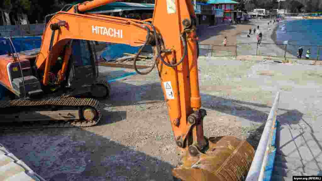 Екскаватор використовувався для демонтажу пошкодженого штормами бетонного фундаменту ротонди та укладання колотих скельних валунів уздовж нього