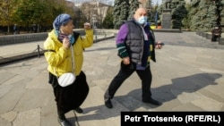 Алматыдағы митингіде өзара тәжікелесіп қалған ер мен әйел. 31 қазан, 2020.