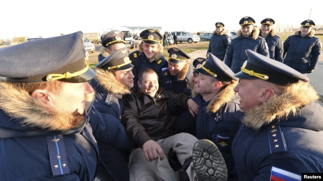 Servicemen welcome military personnel home from Syria at a base in southern Russia.