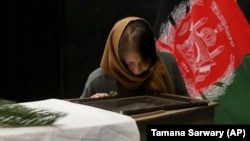 FILE: The wife of slain Japanese physician Tetsu Nakamura looks at the coffin of her husband at the Afghan military hospital in Kabul in December 2019.