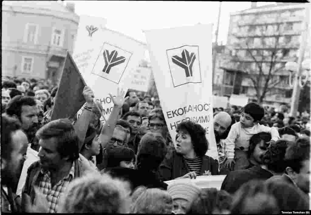 """Пламен Крайски (на преден план вляво, с карираната риза), Владимир Кънев (студентът със знамето и разперените ръце), Вера Младенова (в средата), Едвин Сугарев (вдясно, зад транспаранта). Киноведът Вера Младенова напуска """"Екогласност"""" почти веднага след падането на Живков. В книга, посветена на създаването на сдружението, обяснява, че е искала да членува в екологична организация, докато """"Екогласност"""" твърде бързо се е оказала политическа формация."""