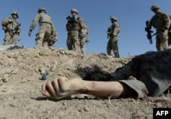 НАТО солдаттары өзін-өзі жарған жанкештінің мәйітіне қарап тұр. Ауғанстан, Вардак провинциясы, 8 қыркүйек 2013 жыл.