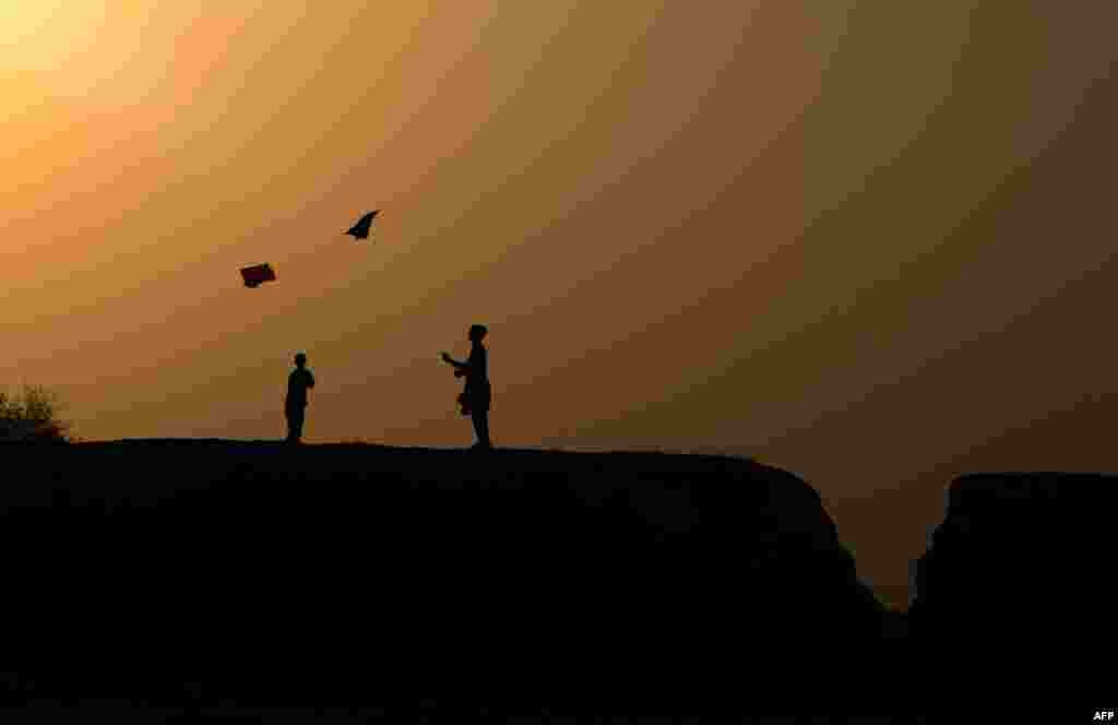 Afghan youths play with a kite on the outskirts of Jalalabad on October 18. (AFP/Noorullah Shirzada)