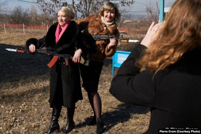 Донецк, 23 февраля 2015. Школьные учительницы позируют с оружием во время празднования Дня защитника Отечества