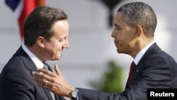 U.S. President Barack Obama (right) greets British Prime Minister David Cameron during an official arrival ceremony for Cameron on the South Lawn of the White House in Washington, D.C., on March 14.