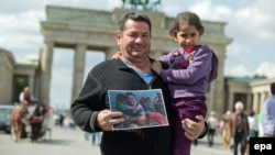 Syrian refugee Laith Majid Al-Amirij and his 7-year-old daughter Noor pose in front of the Brandenburg Gate in Berlin while holding a famous photo showing them during their crossing to the Greek island of Kos.