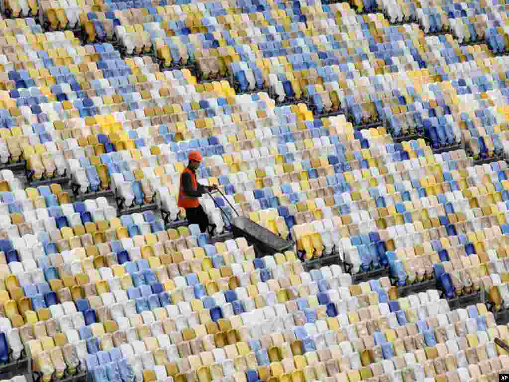 A worker pushes a wheelbarrow past rows of seats as construction continues on September 8 at the Olympiyskiy national stadium, which will host the final soccer match of Euro 2012 in Kyiv. (Photo by Efrem Lukatsky for AP)