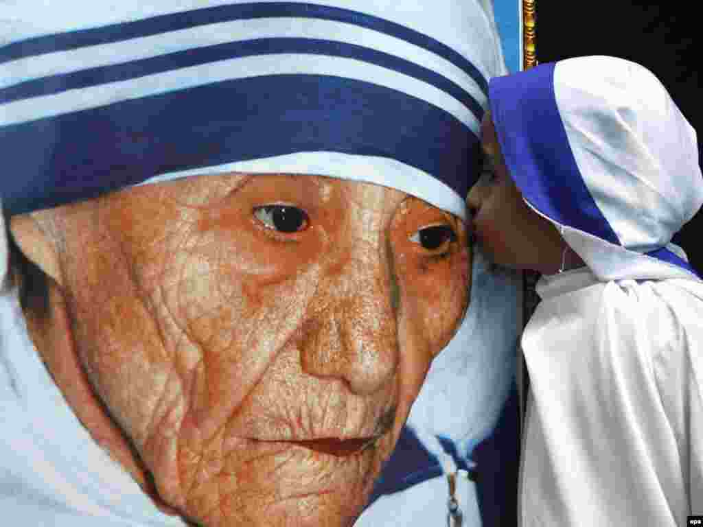 An Indian child dressed as Mother Teresa kisses her portrait during a tribute ceremony during her centenary birth celebrations in Bhopal, India, on August 26. Mother Teresa founded the order in 1950 and devoted herself to the cause of the poor, infirm, and the dying worldwide from her base in Calcutta. Mother Teresa died in 1997. Photo by Sanjeev Gupta for epa